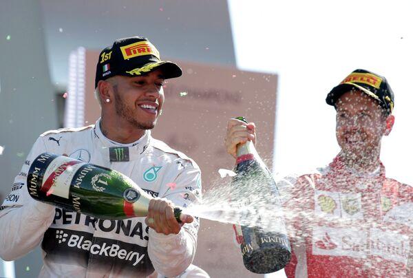 Пилот команды Ф-1 Мерседес Льюис Хэмилтон и гонщик Феррари Себастьян Феттель (слева направо)