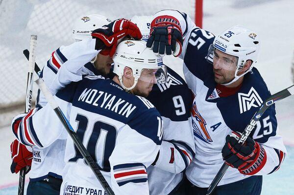 Хоккеисты Металлурга Сергей Мозякин (в центре), Данис Зарипов (справа) радуются забитой шайбе