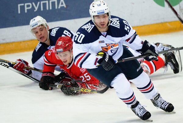 Форвард Автомобилиста Виталий Попов (в центре) и нападающий Металлурга Алексей Кайгородов (справа)