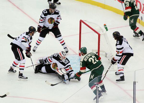 Форвард Миннесоты Нино Нидеррайтер (третий справа) забрасывает шайбу в ворота Чикаго в матче НХЛ на открытом воздухе