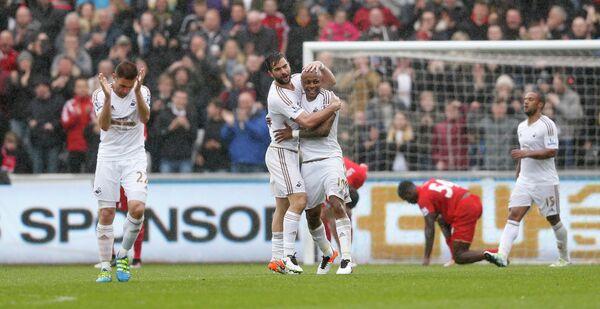 Футболисты Суонси радуются забитому мячу Андре Айю (в центре)