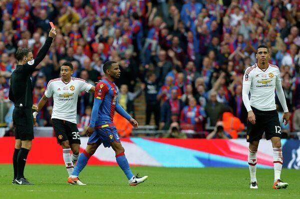 Главный арбитр матча Марк Клаттенбург показывает красную карточку защитнику Манчестер Юнайтед Крису Смоллингу (справа)