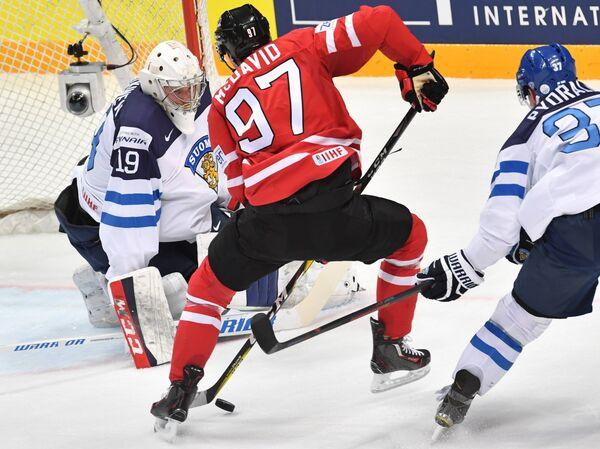 Вратарь сборной Финляндии Микко Коскинен, форвард сборной Канады Коннор Макдэвид и нападающий сборной Финляндии Мика Пюёряля (слева направо)