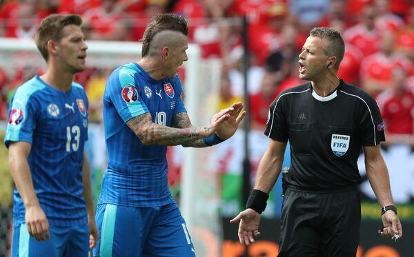 Полузащитник сборной Словакии Юрай Куцка (в центре) и главный судья Свейн Оддвар Моэн (справа)