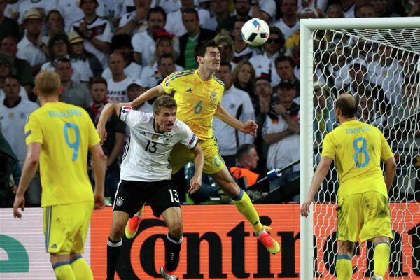 Форвард сборной Германии Томас Мюллер и полузащитник сборной Украины Тарас Степаненко (слева направо на втором плане)